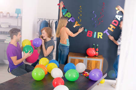 surprise party: Bunch of friends preparing decorations for surprise birthday party