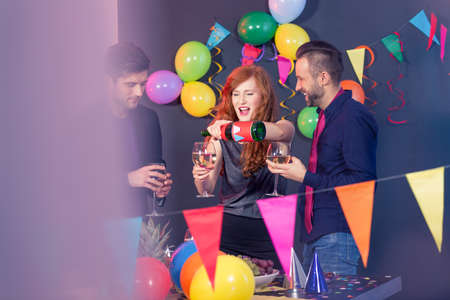 flirt: Pretty young girl drinking champagne with her friends on a birthday party Stock Photo
