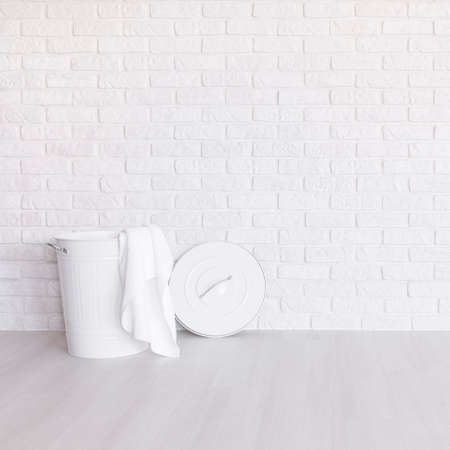 laundry room: White laundry basket standing in spacious room with light flooring and brick wall Stock Photo
