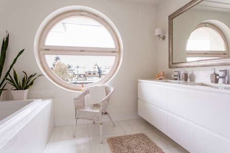 hause: Modern, white bathroom with large round window, mirror, bathtub and chair Stock Photo
