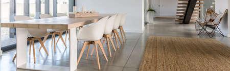 グレーのモダンなダイニング ホールで大きな木製のダイニング テーブル