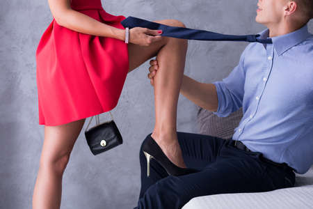 bed skirt: Woman in red dress flirting with the man wearing tie and elegant shirt Stock Photo