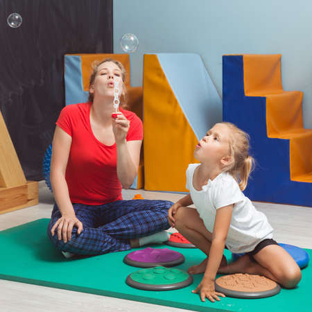 Child and therapist blowing bubbles during sensory integration therapy
