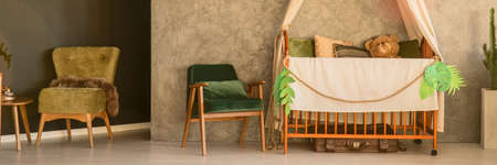 baby bed: Room with simple, wood cot and kale green armchair, panorama