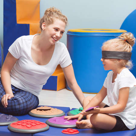 School girl with closed eyes during sensory integration class with therapist