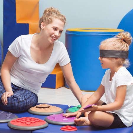 치료와 감각 통합 수업 중 닫힌 된 눈을 가진 학교 소녀