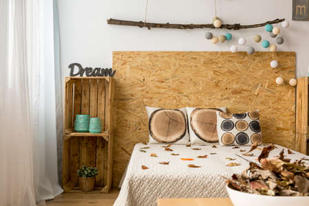 double bed: Cozy bedroom in autumnal tones with double bed and wooden boxes as DIY furniture