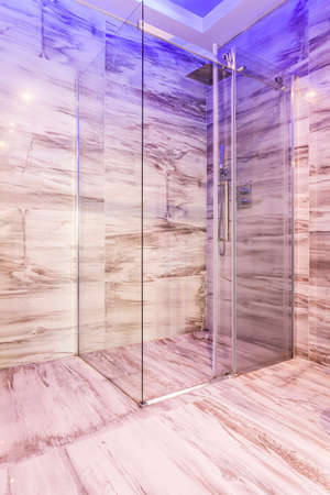 steely: Transparent glass shower stall with blue lighting in marble bathroom