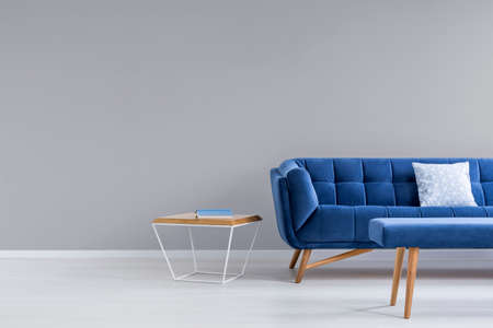 Grey room with blue couch, bench and side table Stock Photo
