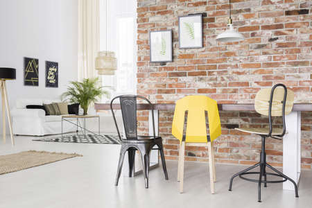 Modern apartment with brick wall, dining table, chair and sofa