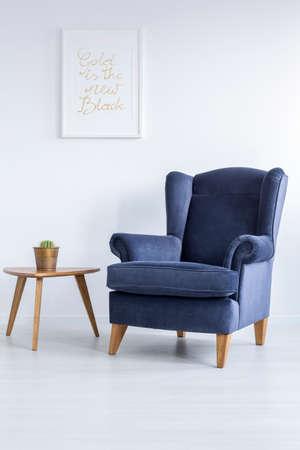 habitación blanca con sillón tapizado de azul y mesa auxiliar Foto de archivo