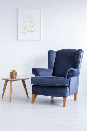 White room with blue upholstered armchair and side table