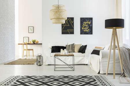 Bílý domácí interiér s pohovkou, stolem, lampou a kobercem