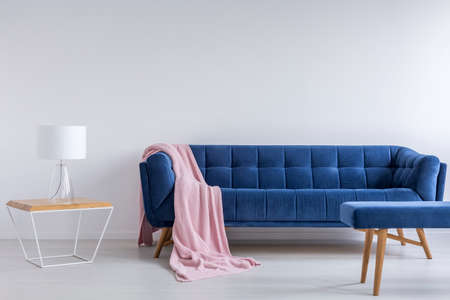 upholstered: White interior with blue sofa, lamp, bench and table