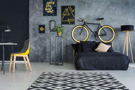 Grijze multifunctionele ruimte met bed, bureau, stoel en wanddecoratie Stockfoto