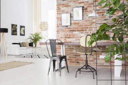 식탁, 벽돌 벽 및 녹색 식물이있는 로프트 실내 스톡 콘텐츠