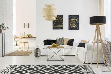 白いソファ、テーブル、パターン カーペット、ランプが明るい部屋