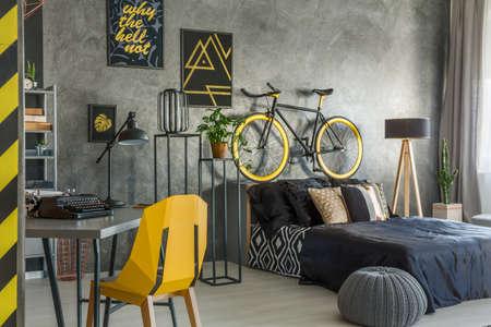 Hipster flat in grijs met kantoor en slaapkamer gecombineerd Stockfoto - 71340259