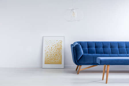 living room wall: White living room with blue sofa, bench and wall poster