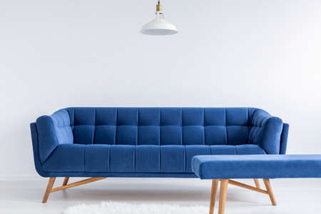 wall design: Ascetic white room with lamp, blue vintage sofa and bench