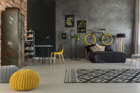 Grey apartment with bed, desk, chair, brick wall, yellow details Stock Photo