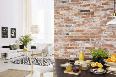 Dining room open to bright living room with sofa 스톡 콘텐츠