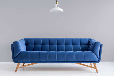 Grey interior with stylish upholstered blue sofa and lamp