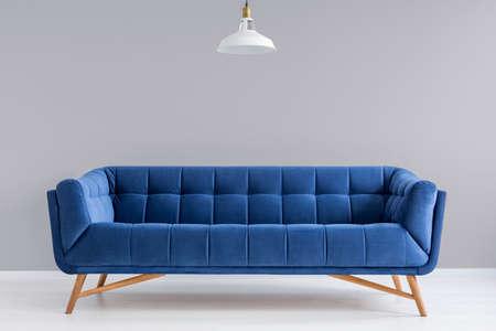 Grijze interieur met stijlvolle gestoffeerde blauwe sofa en een lamp