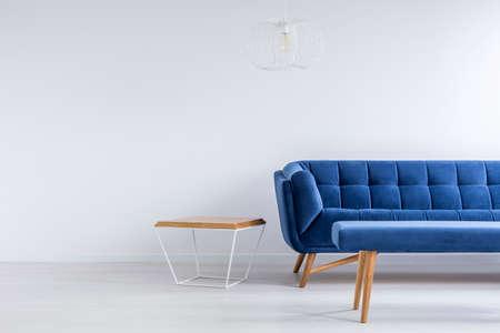 azul marino: Habitación con sofá azul, banco, mesa de metal y madera Foto de archivo