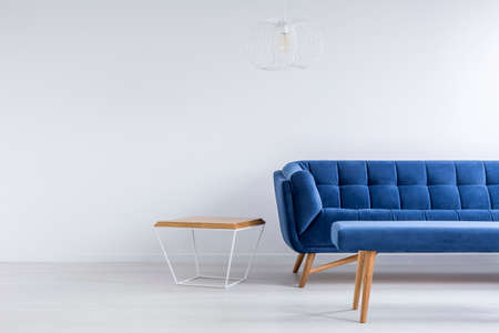 Room with blue sofa, bench, metal and wood table Фото со стока