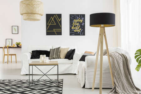 Trendy woonkamer met witte bank, zwarte lamp en tafel