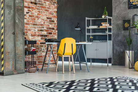 Loft interior with brick wall, desk, yellow chair and bookcase Фото со стока