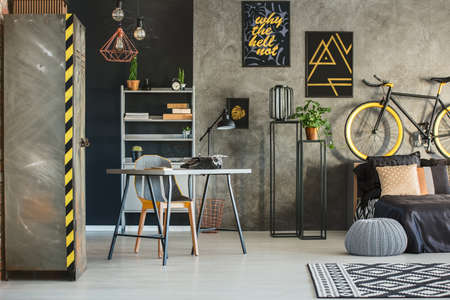 침대, 책상 및 금속 옷장이있는 산업 스타일의 플랫