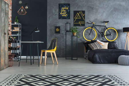 Hipster bedroom with bed, desk, chair and brick wall