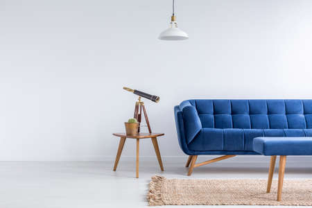 Bright apartment with blue sofa, bench, rug, lamp and table Stock fotó