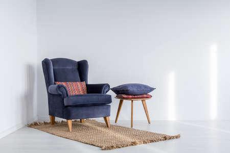 Wit interieur met donkerblauwe fauteuil, tapijt en bijzettafel Stockfoto