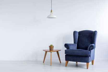 Bright interior with blue armchair, ceiling lamp and side table Foto de archivo