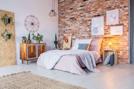 Bright bedroom with double bed, brick wall and rug Stockfoto