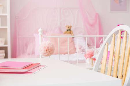 camera ragazza luminosa con scrivania, sedia e letto a baldacchino rosa,