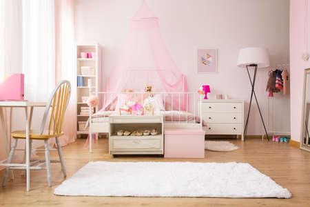 Multifunctionele meisjeskamer met bed, tapijt, stoel en bureau Stockfoto