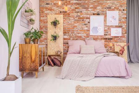 Slaapkamer met een tweepersoonsbed, bakstenen muur en groene decoratieve planten Stockfoto