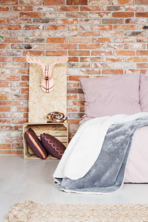 nightstand: Modern bedroom with crate nightstand and brick wall