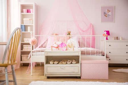 camera da letto rosa con letto a baldacchino e mobili bianchi