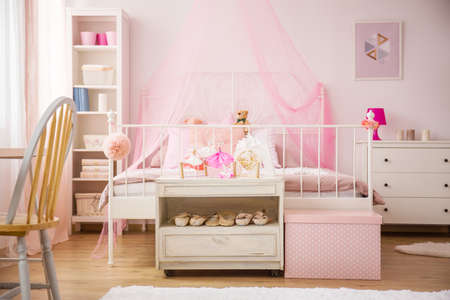 bedroom furniture: Pink bedroom with canopy bed and white furniture