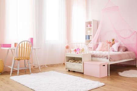 Piccola stanza da principessa rosa con letto a baldacchino, scrivania e sedia