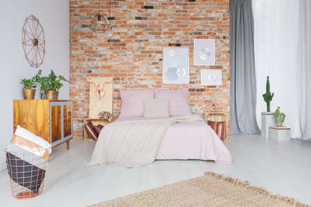 interior decor: Industrial style bedroom with copper accessories and brick wall