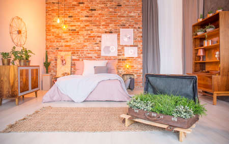 Room with bed and creative suitcase flower pot