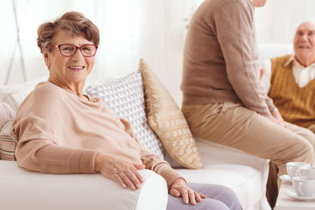 common room: Happy elderly woman sitting on a sofa in retirement club
