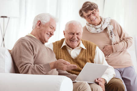Two older men and a woman looking at old photos on a laptop