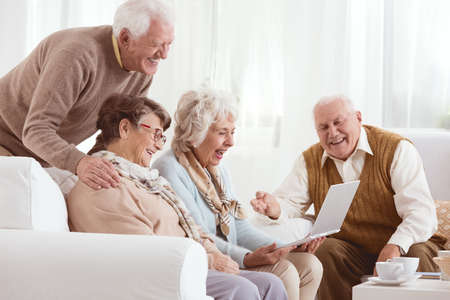 Senior amis regardent ensemble de vieilles photos sur un ordinateur portable